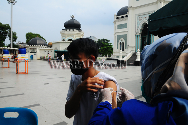 Warga menerima suntikan vaksin Covid dosis pertama yang dilaksanakan di halaman Masjid Al Mashun Medan, Selasa (7/9). Vaksinasi serentak ini merupakan sinergi Polri dan Staf Khusus Presiden RI. (WOL Photo/Ega Ibra)