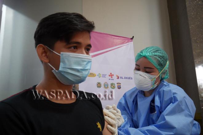 Vaksinator memberikan suntikan vaksin Covid-19 kepada masyarakat yang menerima vaksin di Sentra Vaksinasi Indonesia Bangkit (SVIB), di RSUP H Adam Malik, Medan, Jumat (1/10). Pelaksanaan program vaksinasi yang diinisiasi oleh PT XL Axiata Tbk (XL Axiata) ini telah memberikan suntikan vaksin Covid-19 kepada 12.050 warga. (WOL Photo/Ega Ibra)